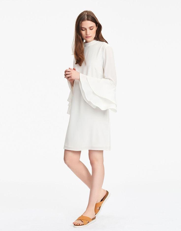 Knälång klänning i rak modell med hög ringning. Utsvängd ärm med volanger och fint utfall från armbågen. Stängs med dragkedja i ryggen.