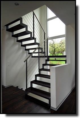 Escalier à limon métallique en crémaillère  Ferro, main courante en inox et marches en bois teinté.