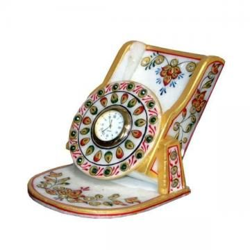 This floral mobile stand with watch is a masterpiece. The kundan work embossed on white marble carving is unrivalled piece of craftsmanship. It is adorned with meenakari, kundan work, and traditional colors. Being a marvelous work of art, it is a superb gift item too.