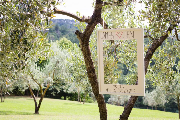 Polaroid style photo booth hanging from olive trees. Wedding day at Villa Nozzole. Tuscany, Italy