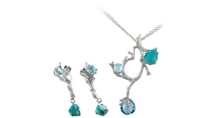 The Sylvan Set embodies a love for the forest with its whimsical loops and swirls that are evocative of leafy vines trailing down from trees. This two-piece set, consisting of a pendant and earrings, is cleverly crafted from silver to give the pieces a vintage look. Accentuating the pieces are gemstones of blue topaz and raw apatite, their luminous colour reflecting clear blue skies. The refined grace of the set can complement a variety of outfits and moods.