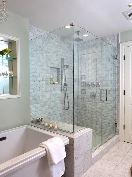 """""""The master bathroom soaker tub is the focal point of the bathroom with a frameless shower glass enclosure detail to allow for a perfect view of the tub upon entry. The perfect amount of grey and sea foam green marble tiling detail at the vanity areas creates interest and adds to the serenity."""""""