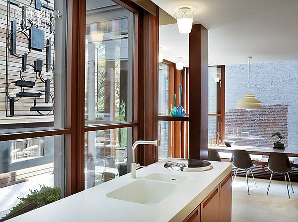 All the World's a Stage: Michael Haverland Revives A Triplex In Gramercy Square | The Corian-topped kitchen island hasa view of the lower terrace's French 1960's wrought-iron screen. #design #interiordesign #interiordesignmagazine #architecture #kitchen #decor
