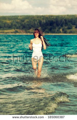 Colorized vintage outdoor portrait of Young beautiful slavonic girl in white top and panties running in coastal waves - stock photo