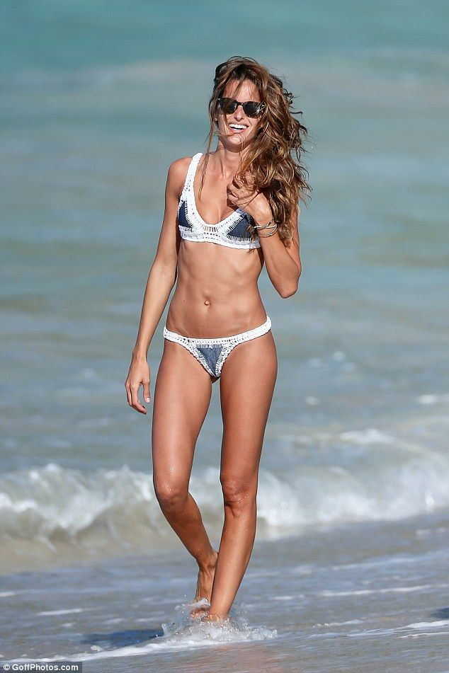 Beach babe: Izabel Goulart, 32, cemented her Brazilian bombshell status as she frolicked on the beach in St Barts in a tiny crochet and denim bikini on Sunday