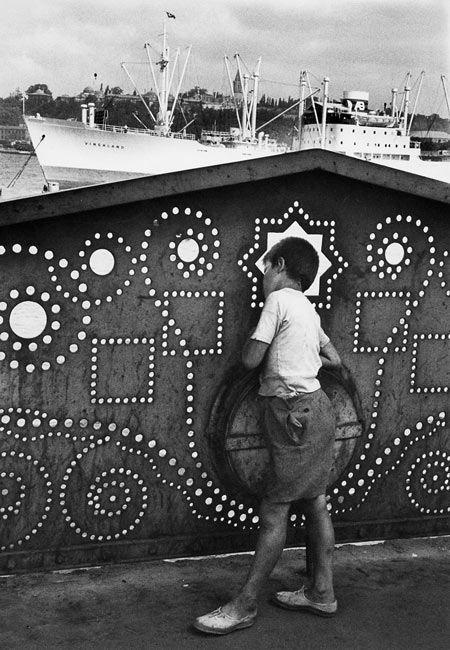 Istanbul, 1955. A travers la dentelle du pont de Galata, sur la Corne d'Or, ce…