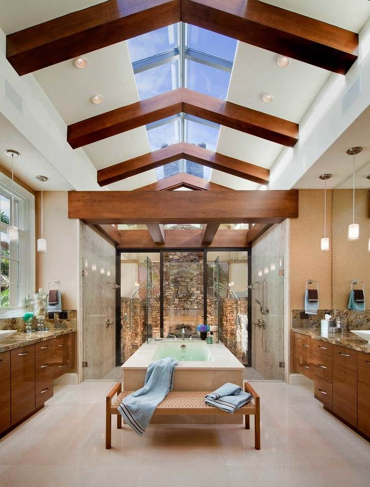 """""""His and hers"""" bathroom with dual showers that look onto a stone fireplace…"""