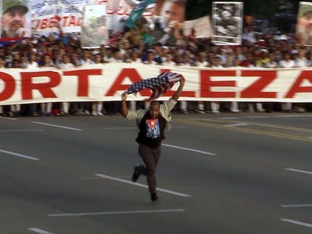 A Cuban dissident interrupted Monday;s May Day parade in Havana, running in front of the marching throngs waving an American flag.