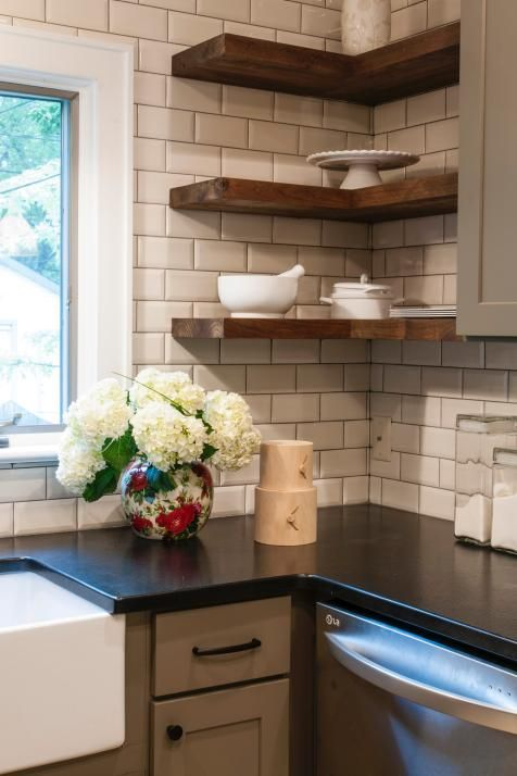 Black kitchen countertops crisply contrast a white subway tile backsplash for a look that's fresh and simple. Floating wood shelves bring in a softer, organic note.
