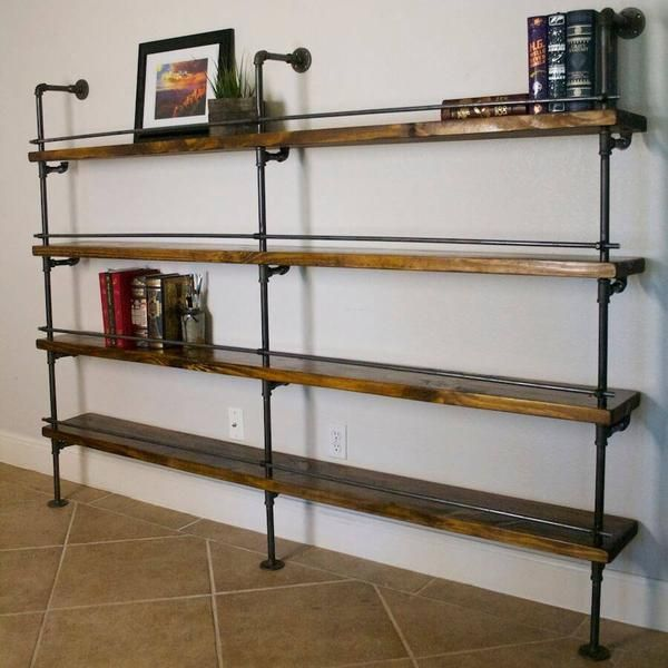 """This industrial pipe shelving includes a bottle stop bar. This is great for library shelving or to hold liquor. This shelving concept was originally purchased by Marriott Hotels for their shipping container bar. The goal of this piece was to be used as above-bar shelving and includes a removable bottle stop. This industrial bookcase is also great for home offices. The pipe is 1/2"""" and unfinished, and the wood shelves are beautiful knotty pine stained medium walnut and finished in satin…"""