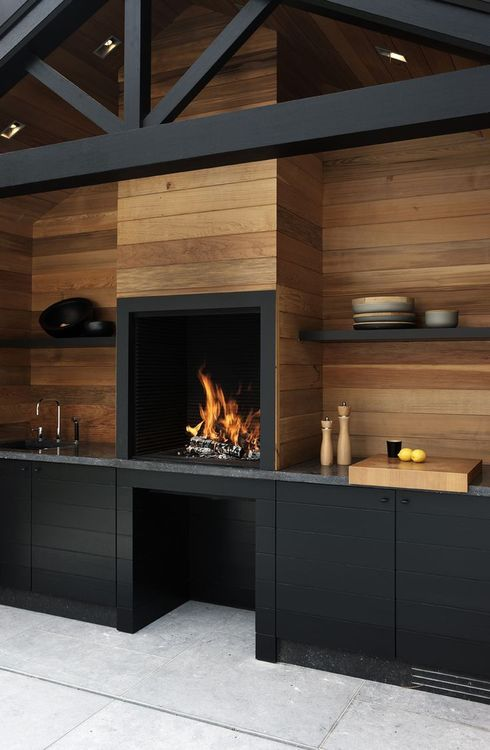 Love the wood walls and raised fireplace in a kitchen
