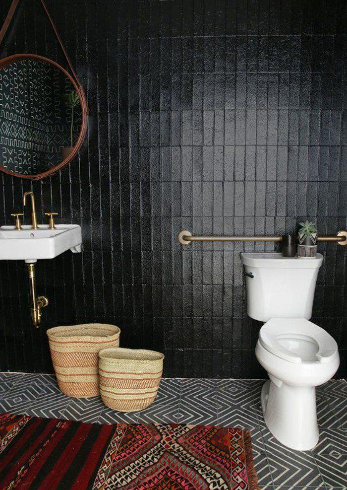 salle de bain chic avec mur en carrelage noir, tapis coloré, salle de bain noire avec miroir rond