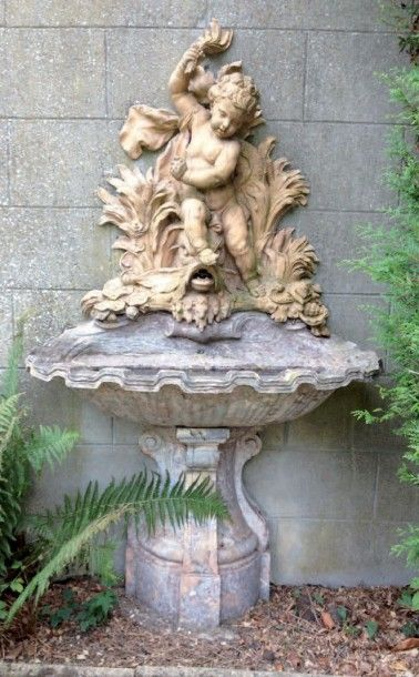 Fontaine en marbre brèche pour le bassin, la partie haute en terre cuite figurant un putto reposant sur un dauphin. 18ème siècle. (Accidents). - May Duhamel - 22/06/2015