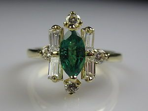 "18K Emerald and Diamond Estate Ring. 8mm x 4mm/.60ct natural Emerald with a deep green hue. Baguette and Brilliant Diamonds. Uniquely angled Baguettes make this a one of a kind conversation piece. The Diamonds add another .44cttw with a GIA grade G/VVS2. The ring offers approximately 1.04cttw. Weighs 4.02 grams. Measures 1/2"" top to bottom and rises 3/8"" off the finger.  (Seller: treasures_newandold)"