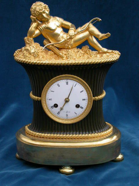 """This fine and rare Empire clock depicts the god of love exhausted after work and resting in a basket filled with grapes and vines. With original fire gilding and green/brown bronze patination to the basket this is a very beautiful clock. Designed by Jean Andre Reiche circa 1807 """"l'amour endormi sur la corbeille"""" this model was housed at the Chateau Fontainebleau in the bed chamber of the Prince of Neuchatel."""