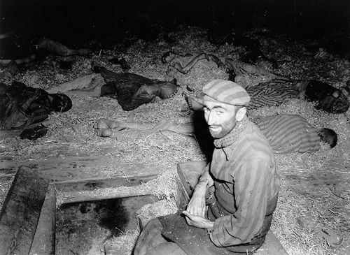 A French Jew at sits amongst the dead at Mittelbau-Dora concentration camp, a sub-camp of Buchenwald concentration camp, following the camp's liberation by the U.S. 3rd Armored Division and various 104th Infantry Division attachments on 11 April 1945. Near Nordhausen, Thuringia, Germany. April 1945.