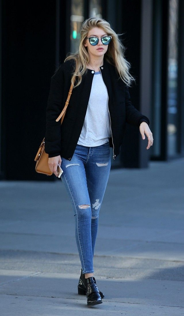 Gigi looks off-duty chic in distressed denim, a simple tee, and a chic bomber jacket.