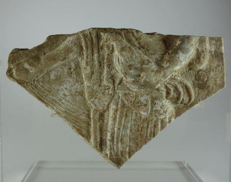 Pinax Locri, 490-460 a.C. Tipo 2/26. Frammento di pinax di Locri raggigurante una figura drappeggiata su un carro che tiene con la mano destra le redini di una biga e con la sinistra tiene un gallo, 10.8 cm x 7 cm. Collezione privata, ex Archea gallery Amsterdam