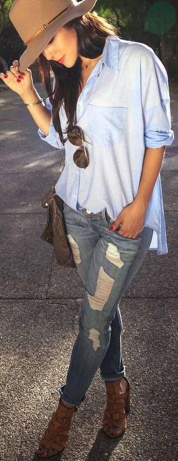 Blusa larga azul fajada solo por enfrente tacones abiertos cafes y sombrero cafe jeans claros y rasgados