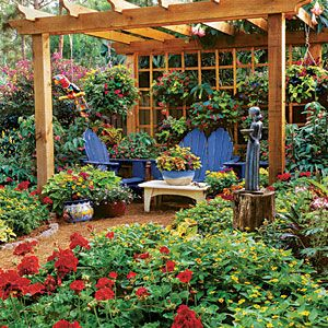 Hanging Annuals—Use an outdoor room, like the space under a pergola, as a place to mix your containers. This grouping has a lush, vibrant mix of planters and hanging pots. | SouthernLiving.com