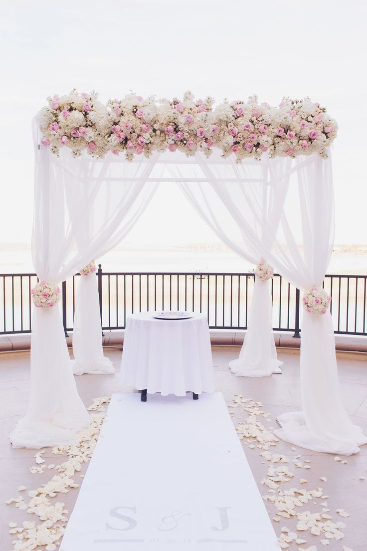 For the lakeside ceremony we dressed a chuppah in flowing ivory fabric topped with ivory and pale pink roses. Matching topiaries lined the aisle. Las Vegas Wedding Planner Andrea Eppolito | Wedding at Lake Las Vegas | White and Blush and Grey Wedding | Luxury Wedding Las Vegas