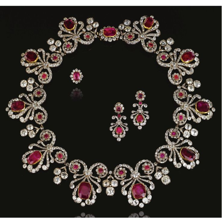FORMERLY THE PROPERTY OF MAJOR HON. BERNARD CLIVE PEARSON Ruby and diamond parure, 1820s and later. The necklace designed as a series of ribbon scrolls set with old-mine, cushion- and rose-cut diamonds, each set to the centre with a cushion-shaped ruby in a cut-down collet and accented with a pair of ruby and diamond florets, interspersed with old-mine diamond trefoil sprigs.