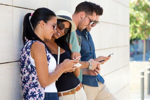 jugando la gente de telefonía móvil jóvenes felices Foto Gratis