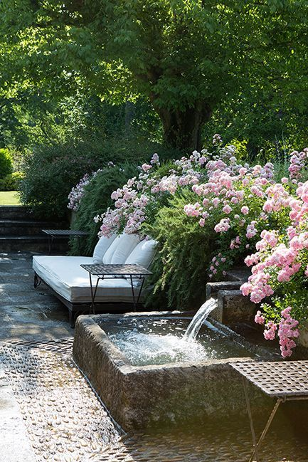 Pink flowers lining the edge of the patio with an upholstered daybed and iron side tables.