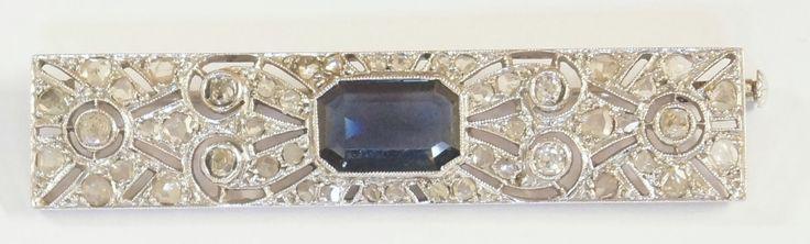 Een 18 krt. witgouden Art deco broche bezet met een grote synthetische saffier en vele diamanten