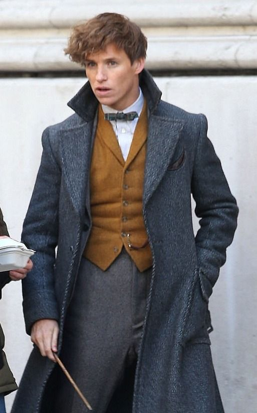 NEW! Wand at the ready, Eddie Redmayne reprises his role of Newt Scamander, shooting on the streets of London Sunday for Fantastic Beasts The Crimes of Grindelwald. Note that the peacock teal greatcoat appears to have given way to a less eccentric gray.