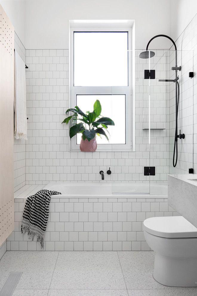 white subway tiles bathtub with black metal shower…