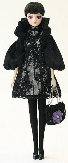 J-Doll Lavalle: She wears a cropped black jacket with puffy sleeves, black lacy knee-length dress over silvery-white fabric, and black hose and pumps complete the look. Her bag is trimmed with a fabric flower with iridescent beads forming its center. Included in the box is a doll stand for display.