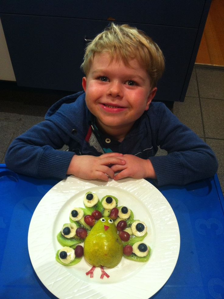 Fruity peacock, made with pear, kiwi fruit, banana, red grapes and blueberries. Eyes made with cream cheese and currants and beak and feet made with red apple skin.