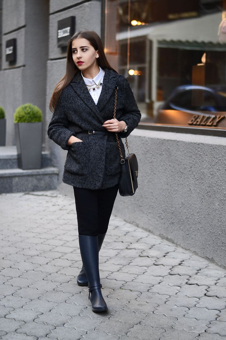 Go for a sophisticated look in a charcoal herringbone coat and black slim pants. Why not add dark blue rain boots to the mix for a more relaxed feel?  Shop this look for $180:  http://lookastic.com/women/looks/coat-satchel-bag-rain-boots-dress-shirt-skinny-pants-belt/6771  — Charcoal Herringbone Coat  — Black Leather Satchel Bag  — Navy Rain Boots  — White Dress Shirt  — Black Skinny Pants  — Black Leather Belt