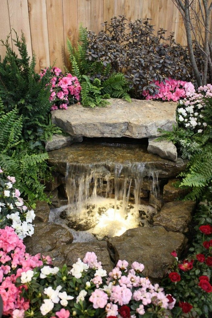 Waterfall colored flowers garden stone wooden garden fence