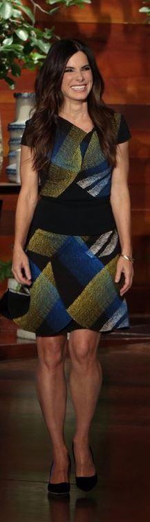 Who made  Sandra Bullock's blue print skirt, green print top, and black pumps?
