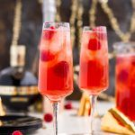New Year's Eve Champagne Punch is loaded with Triple Sec, blackberry brandy, Chambord, pineapple juice, ginger ale, and champagne for a drink that's sure to impress all your NYE party guests!
