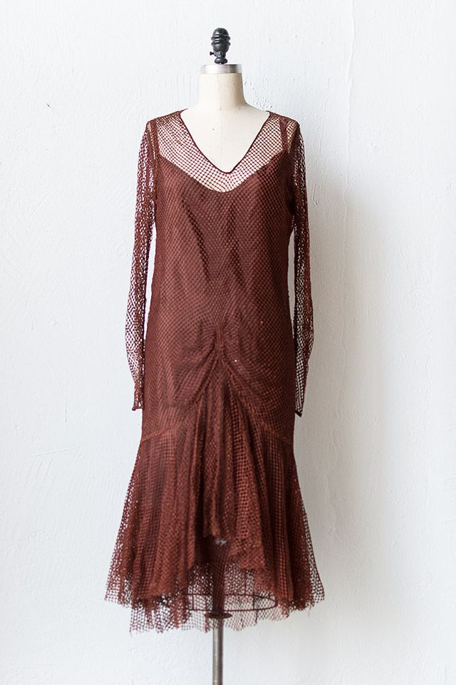 1920s brown net flapper dress features a solid sleeveless brown satin slip with matching netting along the hem and a sheer netting over layer. The sheer layer features long sleeves, v-neckline, and ruching detail at the hips and front that cascade down to a fishtail hem. Both pieces don't have closures and should be pulled on over head.