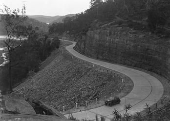 A car drives down the new Pacific Highway near Hawkesbury River, exact date unknown, probably 1920s.