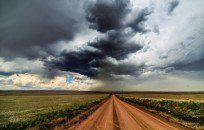 Long Dirt Road Under Storm Clouds HD Desktop Background wallpaper
