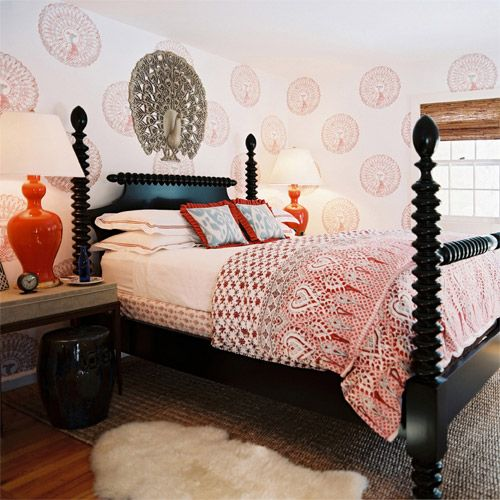 Fun red eclectic bedroom design with red medallion wall stencils, black rope poster bed, glossy black garden stool, seagrass rug, glossy red lamps, blue ikat pillows with red fringe and red bedding.