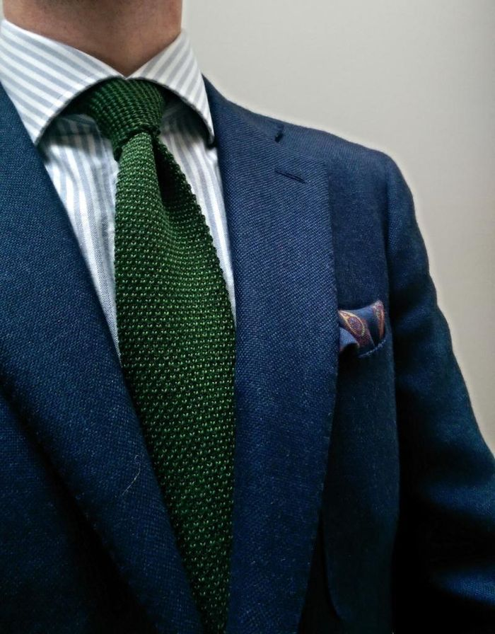 Navy jacket, white shirt with light grey candy stripes, green knit tie
