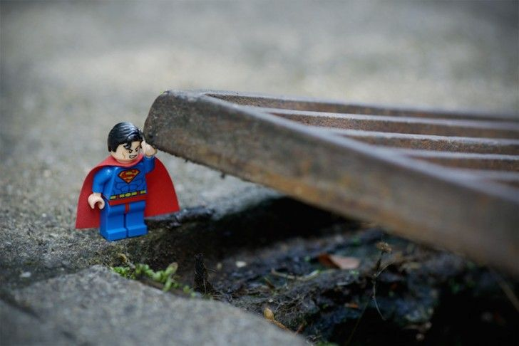 LEGO Superman lifts up a very heavy metal grate with one arm