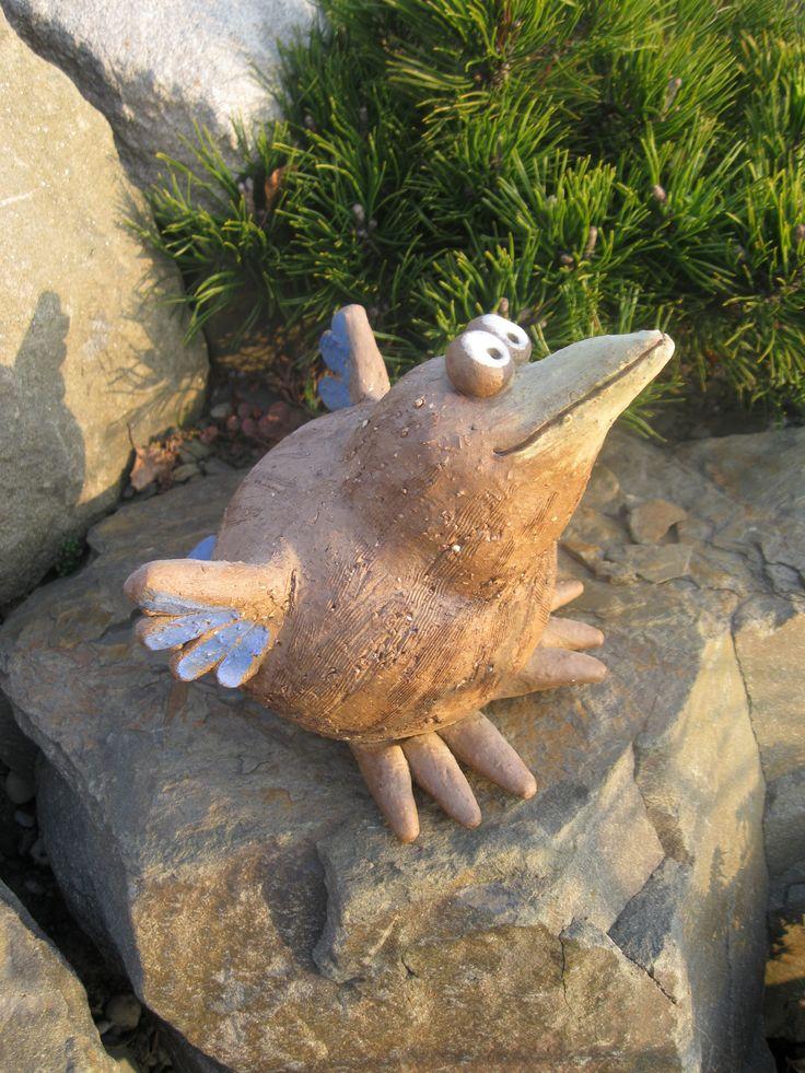 Ptakoš II. Pták z šamotové hlíny, pálený na vysokou teplotu. Barven oxidy, na křídlech dobarven modrou engobou. Velikost zhruba 15 x 18cm.