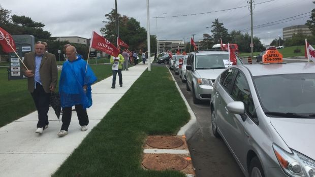 Dozens of Capital Taxi protesters picket outside their dispatcher's headquarters after rejecting a three-year contract offer.
