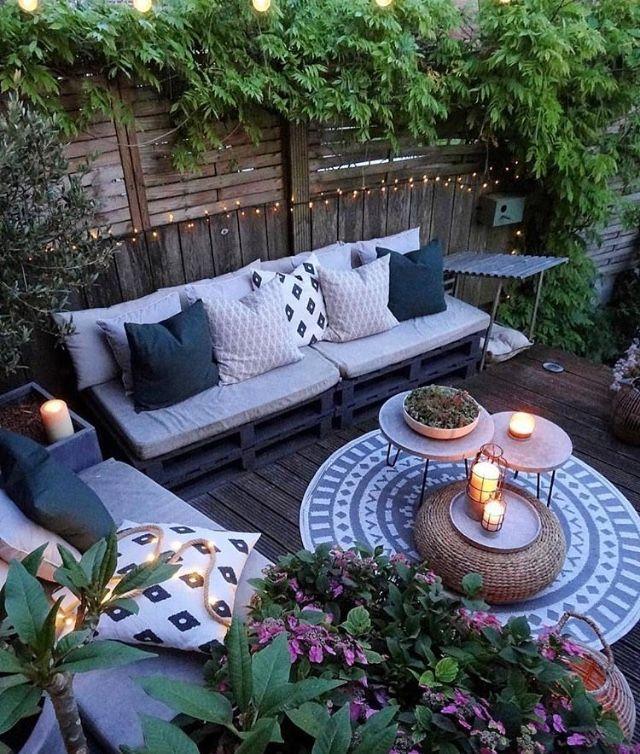 Dekorierte Terrasse mit Teppich und Bank mit Kissen. Gemütliche Atmosphäre mit