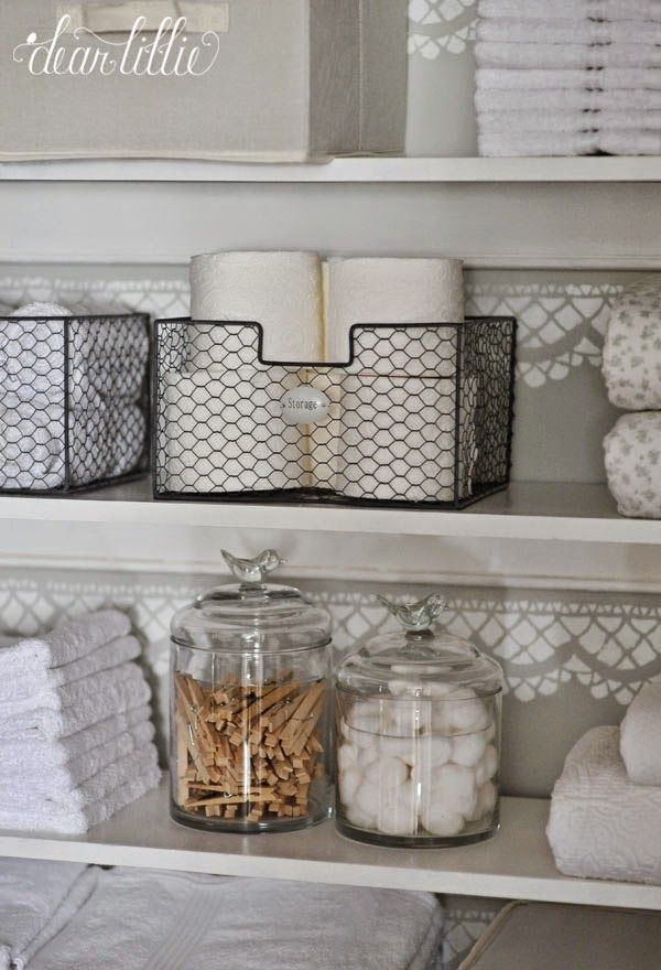Glass jars and wire storage baskets make the shelves of this linen cupboard…
