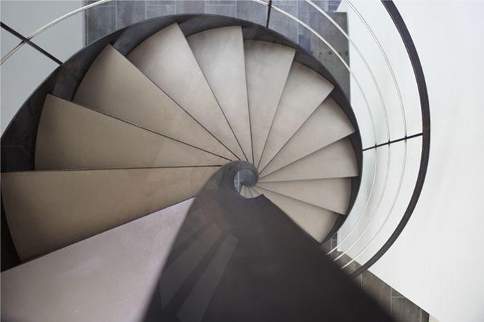 DH99 - SPIR'DÉCO® Flamme. Escalier balancé d'intérieur métallique design sur flamme centrale formant escalier hélicoïdal sans mât central. Marches caisson Nanoacoustic® + tôle lisse en acier inoxydable brossé pour un escalier tout métal silencieux et contemporain. Rampe avec main courante et montants en fer plat, 3 lisses fines en inox brossé. Finition acier brut patiné. - © Photo : Nicolas GRANDMAISON