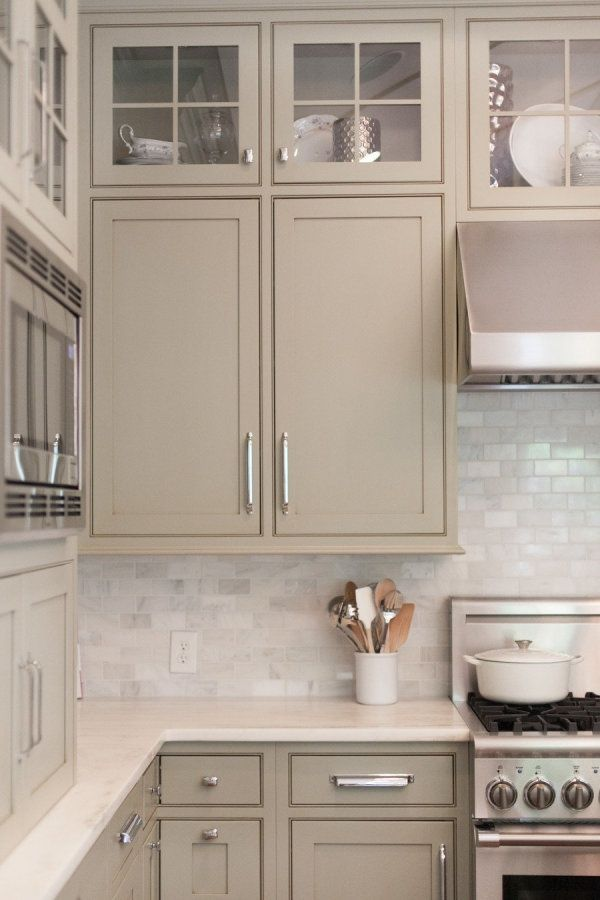 Carrara marble subway tile kitchen backsplash over limestone countertops and lovely taupe cabinets.