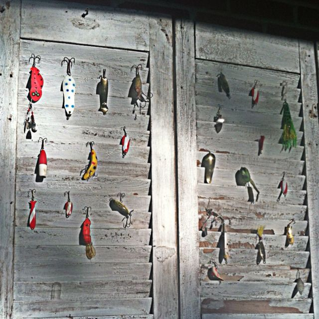 Vintage fishing lures hanging on 100 year old shutters.